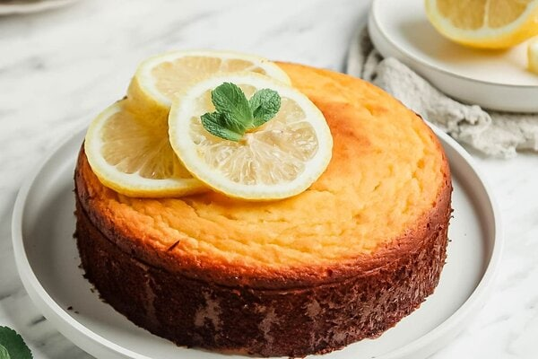Paleo Lemon Cake on large white serving platter topped with 3 lemon slices