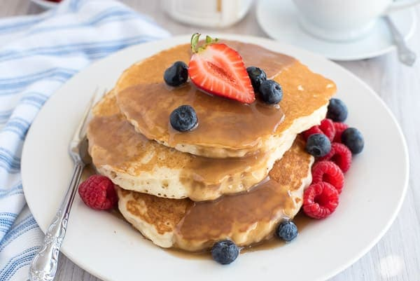 Stack of pancakes with berries and cinnamon syrup