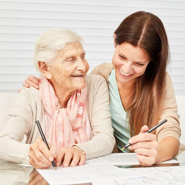 Junge Pflegerin hilft Seniorin