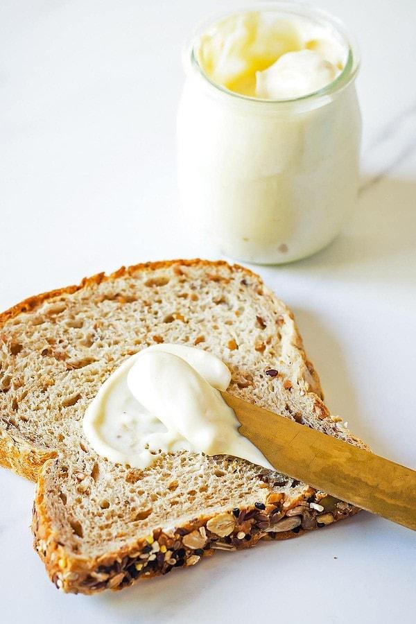 Knife spreading mayonnaise on bread slice