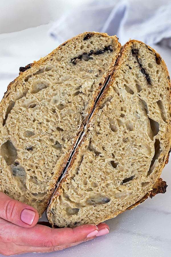 Hand holding homemade sourdough bread cut in half