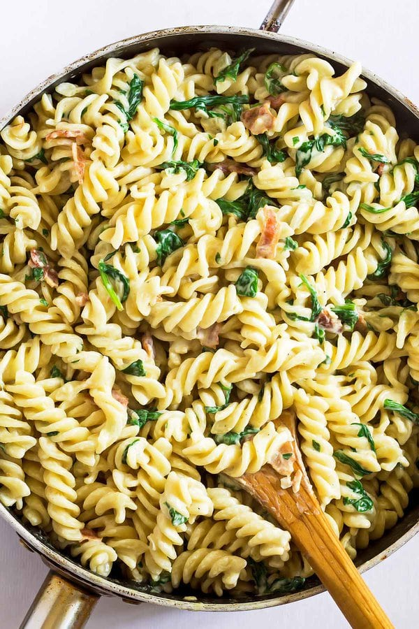Pasta with bacon and cream in pan with wooden spoon