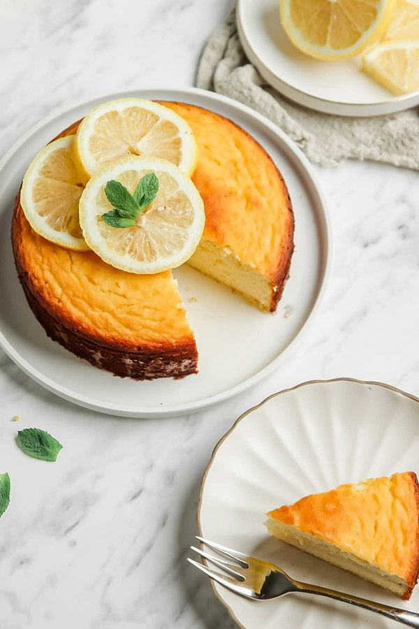 Whole lemon pound cake with 1 slice removed onto small white plate with fork