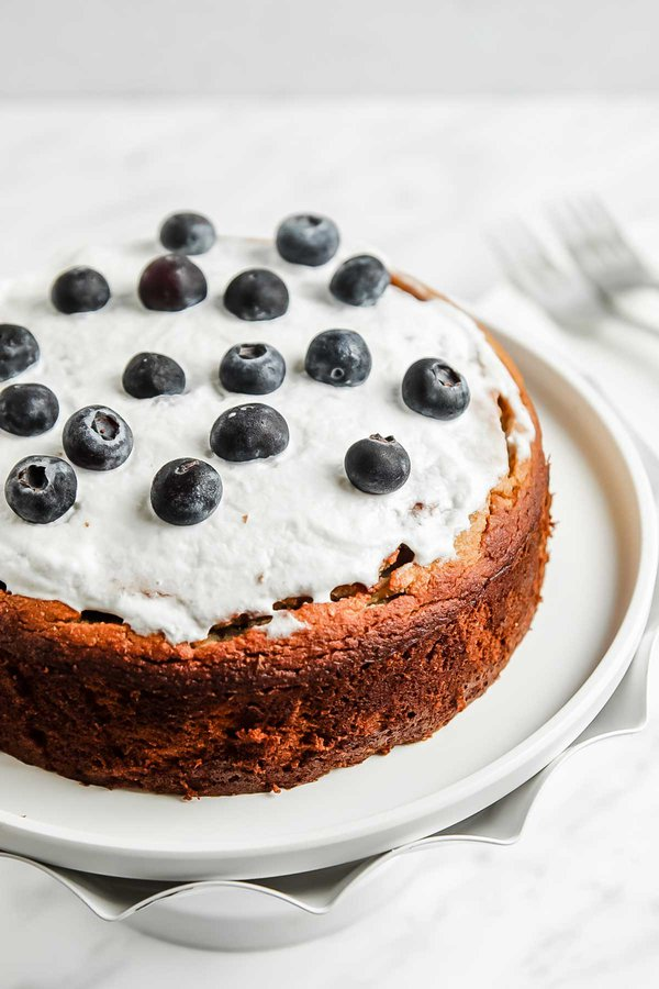 Coconut Flour Cake with banana on cake stand with coconut cream and blueberry topping