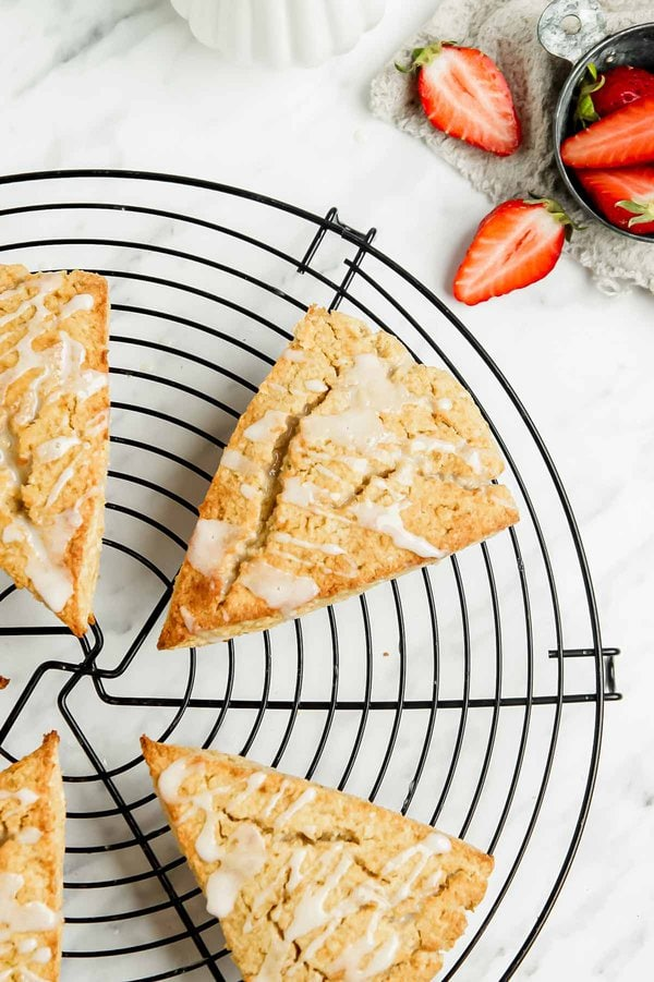 Coconut flour scones on circular wire rack, strawberries on the side