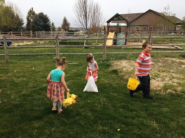 children gathering eggs in their baskets at an Easter egg hunt in backyard