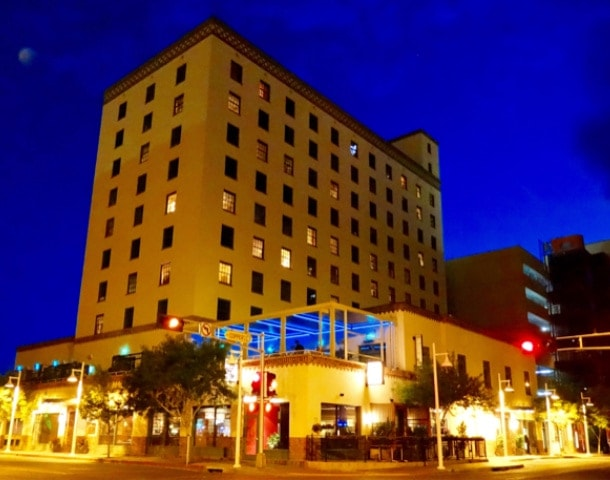 Heavy late-1930s building rises up to night sky. Ground floor is lit with colorful lights at theis cool places to stay in Albuquerque