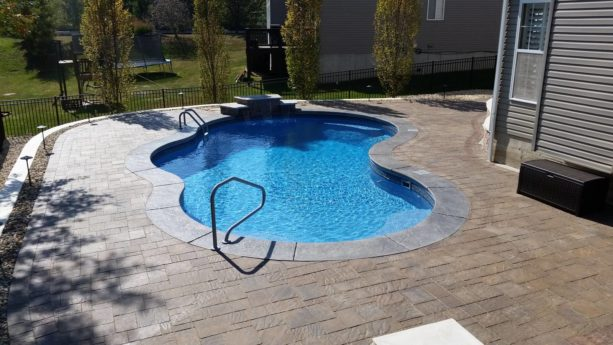 a traditional pool backyard with stamped cantilevered coping concrete around