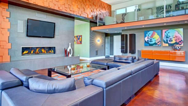exuberant orange wall and silvery blue sectional in an open concept living room