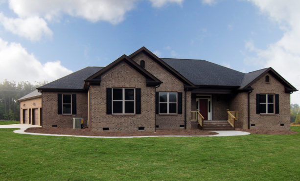 a transitional brown brick house with black shutters