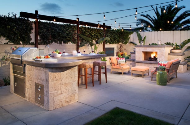 tropical l-shaped outdoor kitchen patio completed with a gas fireplace