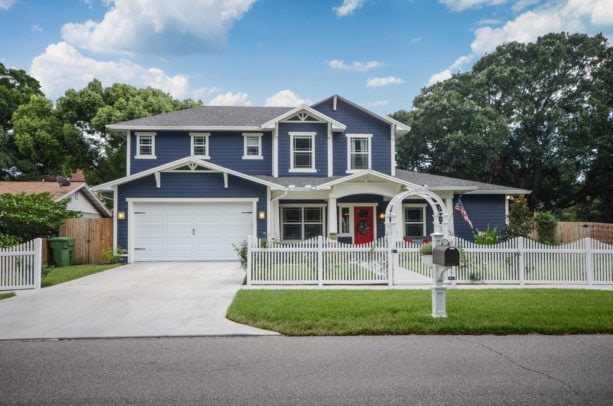 a navy blue house with white trim and red door