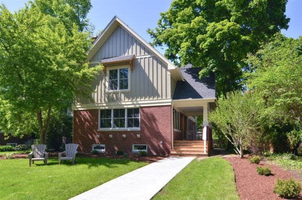 red brick home paired with grey-painted siding on the second floor