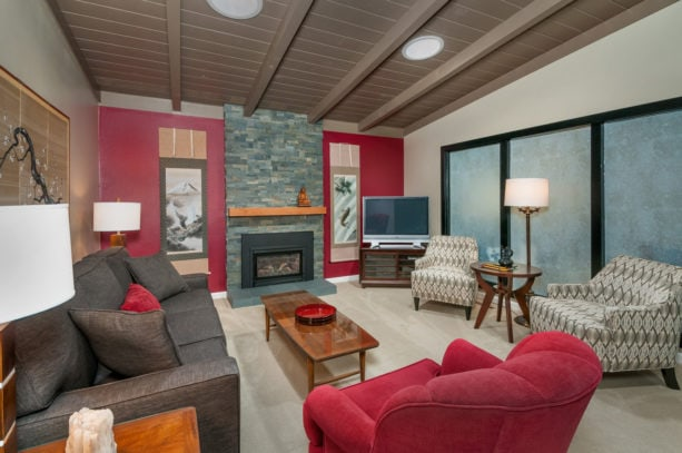 an asian living room with red accent wall and grey fireplace