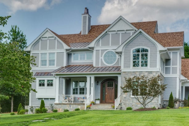 an elegant eclectic traditional light grey house with brown roof
