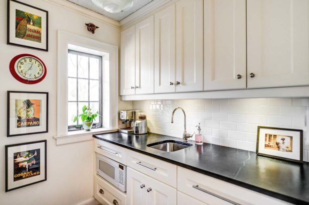 white subway tile and white grout paired with antique white cabinets