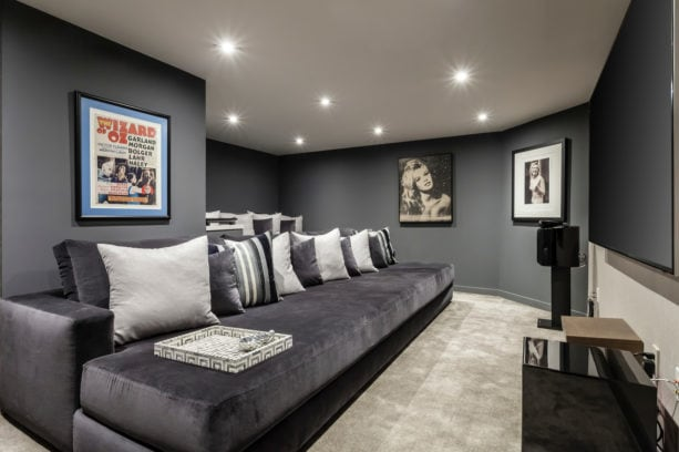 a home theater with dark grey walls and beige carpet floor