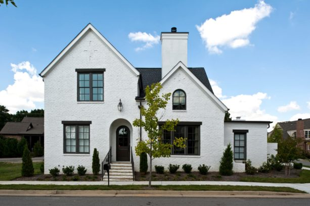 a white brick house with unique and prominent black top trim for the windows
