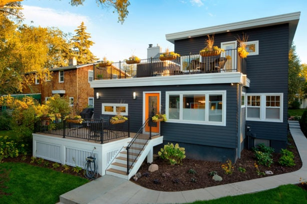 modern ranch style dark charcoal grey vinyl siding exterior house with a shingle roof