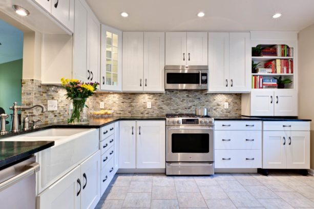 transitional u-shaped kitchen in monochromatic color featuring white cabinets and pebble black countertops
