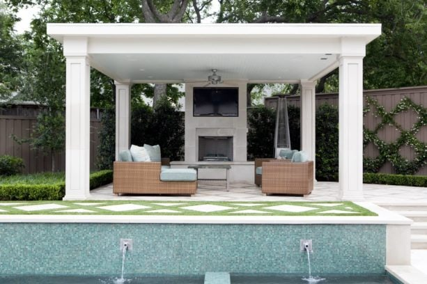 outdoor living room with square white columns and tv above a fireplace