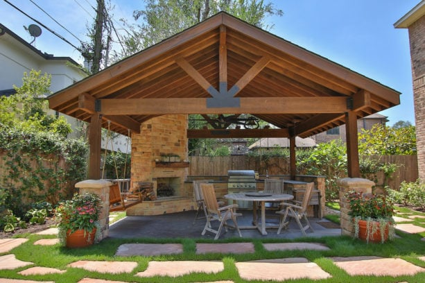 rustic concrete covered patio with masonry wood burning fireplace