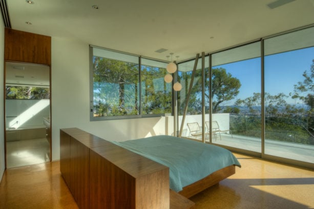 standard double bed with wooden headboard in the middle of a minimalist room