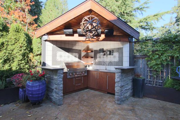 small modern covered outdoor l-shaped kitchen in an open concept design