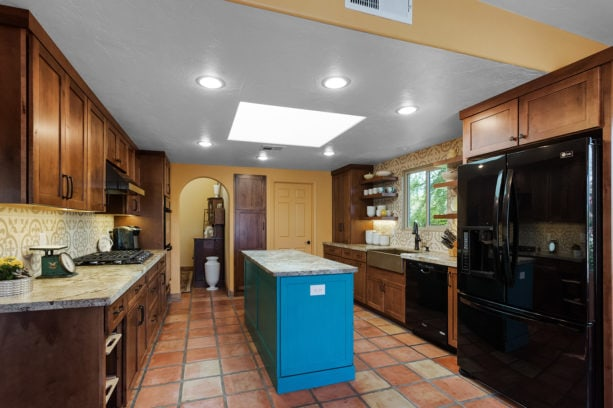 terracotta tile kitchen color combined with turquoise island and brown cabinets to achieve a neutral yet striking look