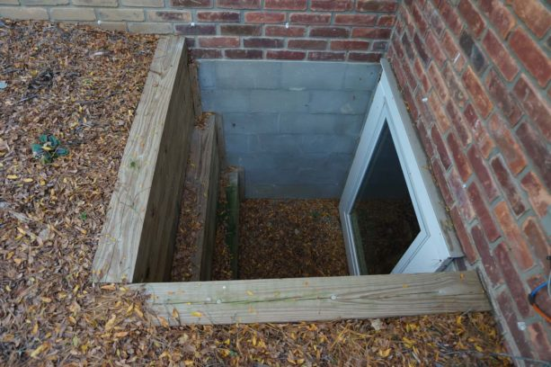 combination of wood, concrete, and brick of a basement window well