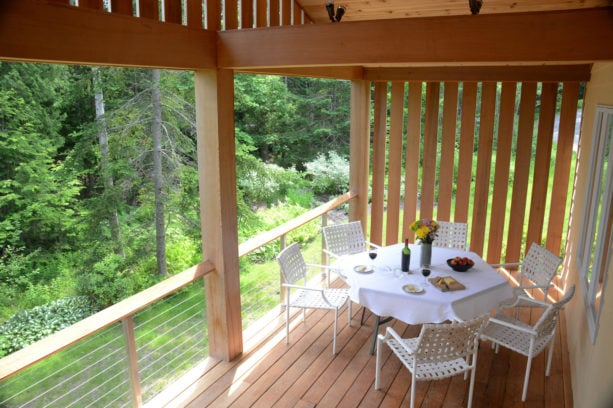 small covered deck with cedar board vertical wood slat wall as a screen