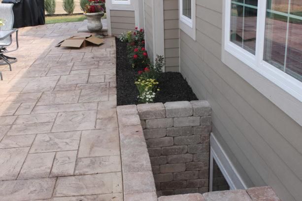 stamped concrete basement window wells in a backyard patio