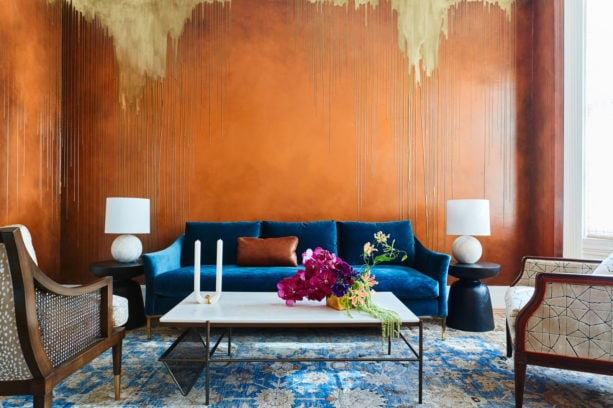 custom finish bronze orange wall mixed with navy blue sofa in a mid-sized living room