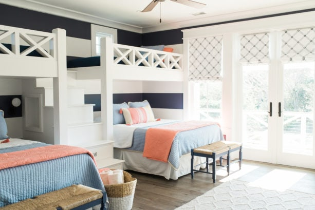 coral and blue shared bedroom with white and navy blue horizontal stripes wall design