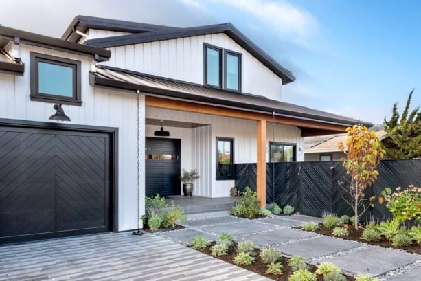 a white farmhouse exterior with black trim and wood accent