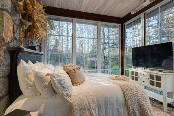 a sunroom with bed, complete with a TV placed right in front of the window