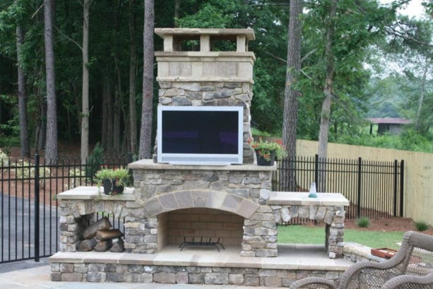 beautiful side yard with DIY outdoor fireplace kit and 36 inch tv