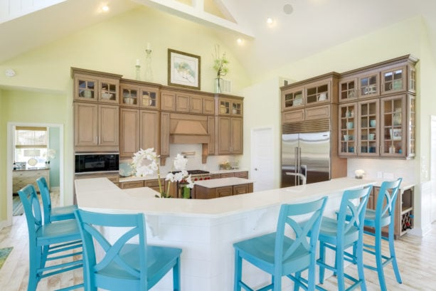 bright blue colored chairs combined with white backsplash and brown glass-front cabinets to add a coastal look in the kitchen