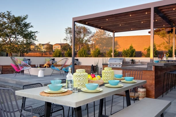 covered outdoor patio kitchen with l-shaped design and open concept dining area