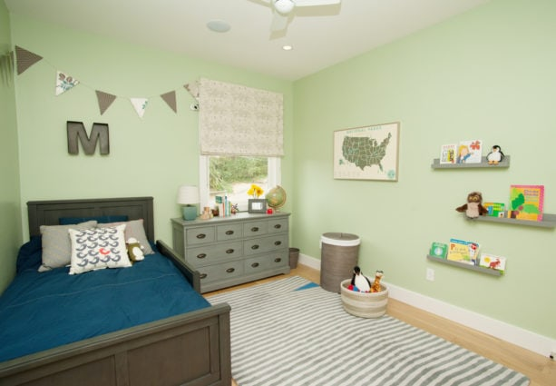 a boy bedroom with pastel green wall paint and grey furniture and decorations