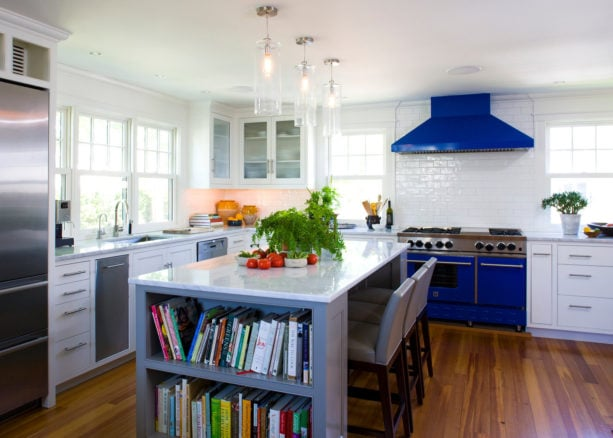 blue stove and range hood with white subway tile backsplash with white grout