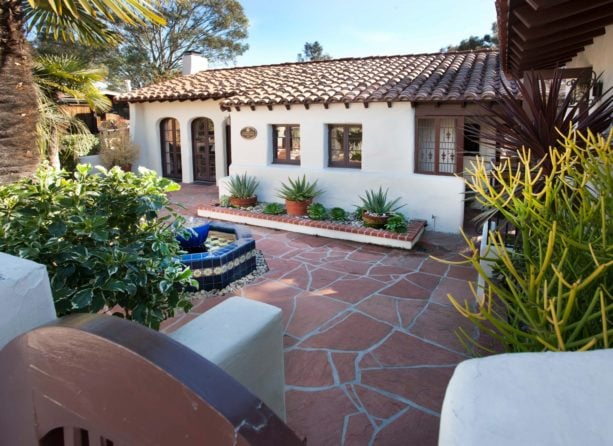 white spanish style home with a mediterranean red sandstone courtyard