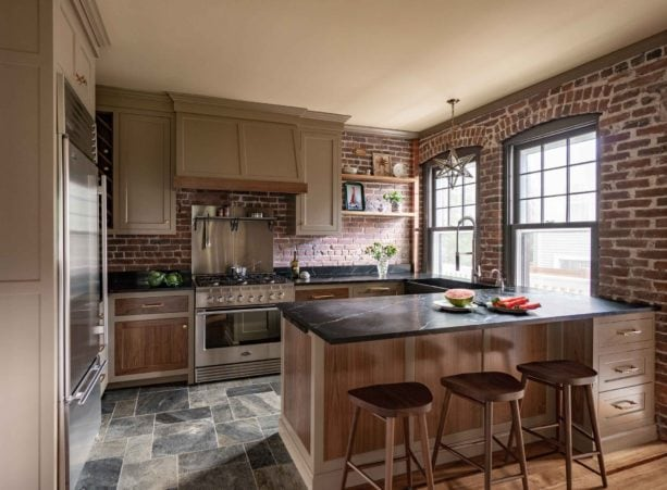 farmhouse style combination of brown shaker cabinets, black soapstone countertops and red-colored brick wall to add more texture in the kitchen