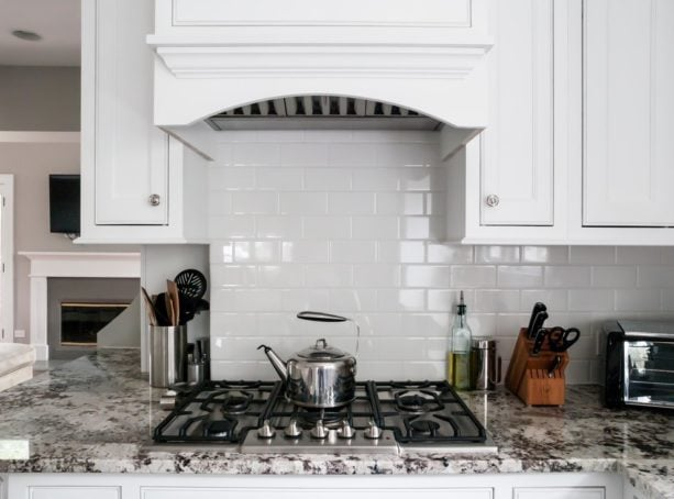 white subway tile backsplash and white grout that look contrast to the stove and countertop