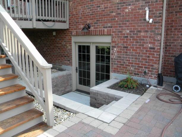 2 panel bi-fold walkout basement door option in a red brick wall