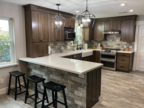 combination of gray travertine backsplash, white countertops kitchen color, and brown shaker cabinets to get cozy sensation