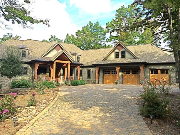 large mountain style green two-story house with brown trim