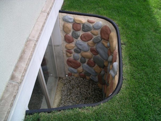 multicolored stone basement window well with black trim