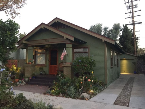 small arts and crafts green one-story stucco gable roof with brown trim