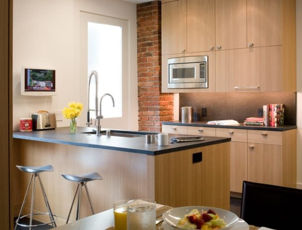 kitchen peninsula with laminate countertops and three-legged stools seating